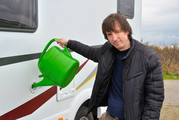 man refilling a fresh water tank during camping
