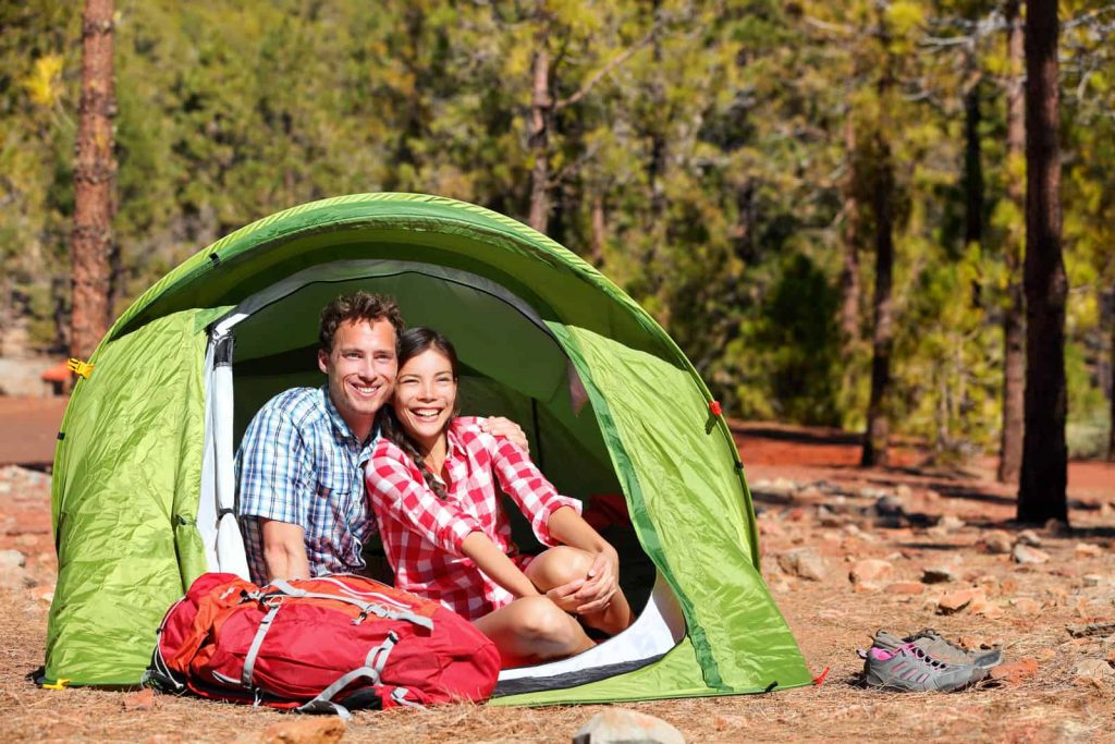couple packing their tent in a backpack