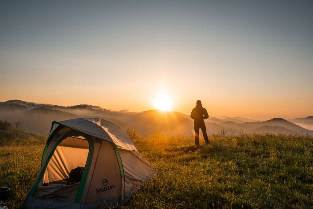 man with 6 person tent under the sunset